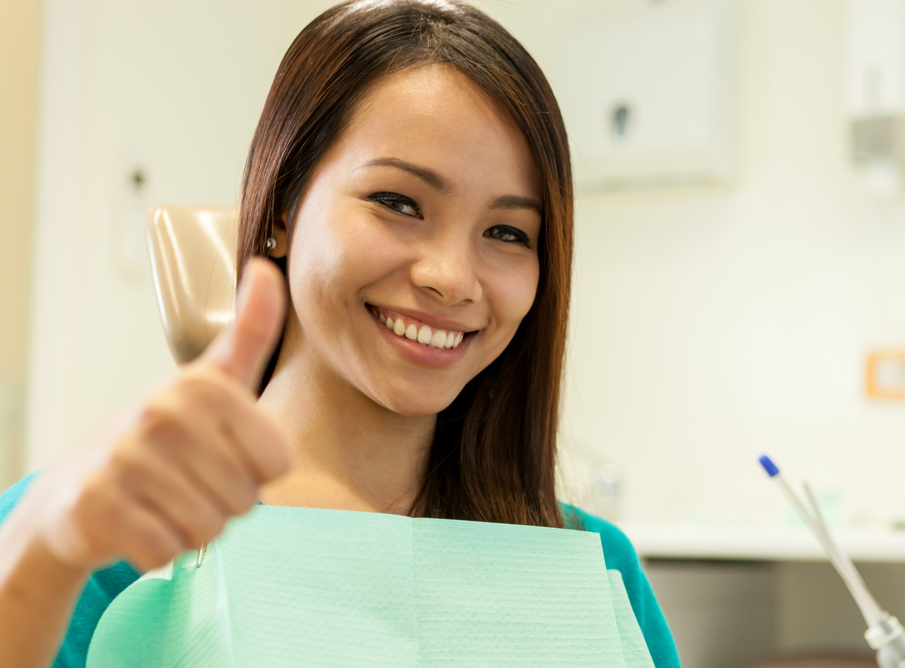 photo of asian young woman sitting at the dentist while smiling towards the camera